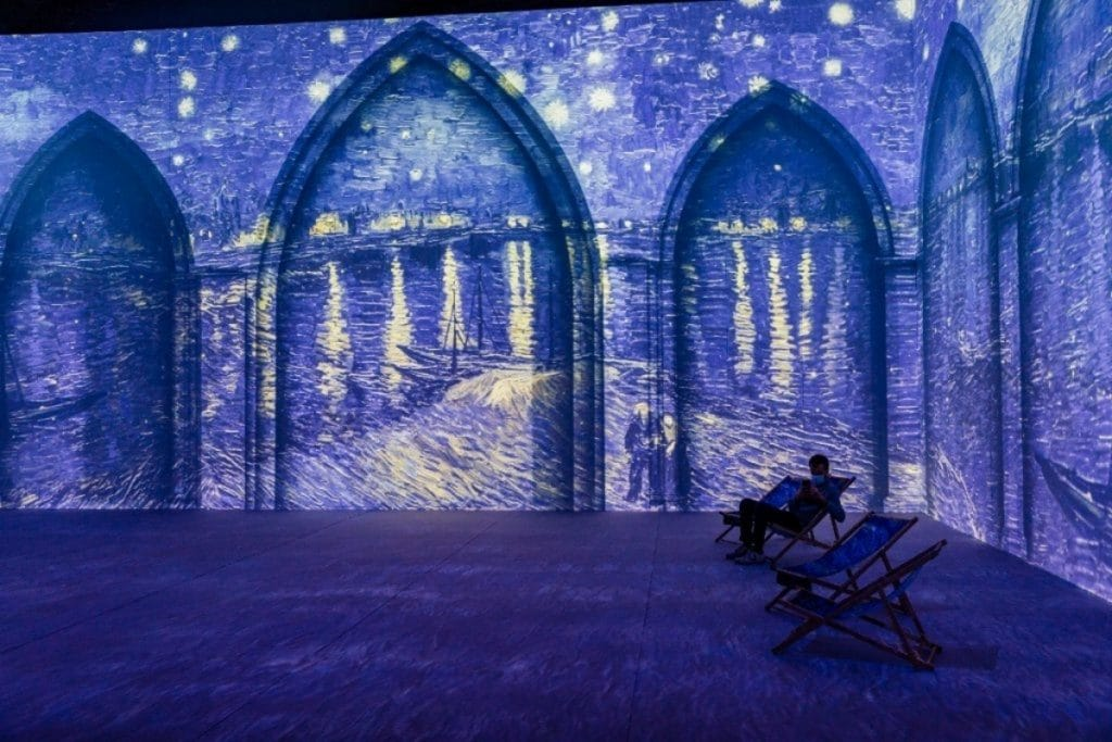 Van Gogh: The Immersive Experience exhibition. Image of Starry Night Over the Rhône on walls and floor of museum.