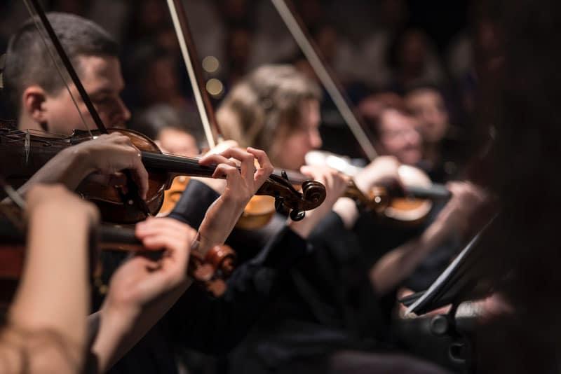 pessoas a tocarem as obras de Beethoven e Vivaldi no violino