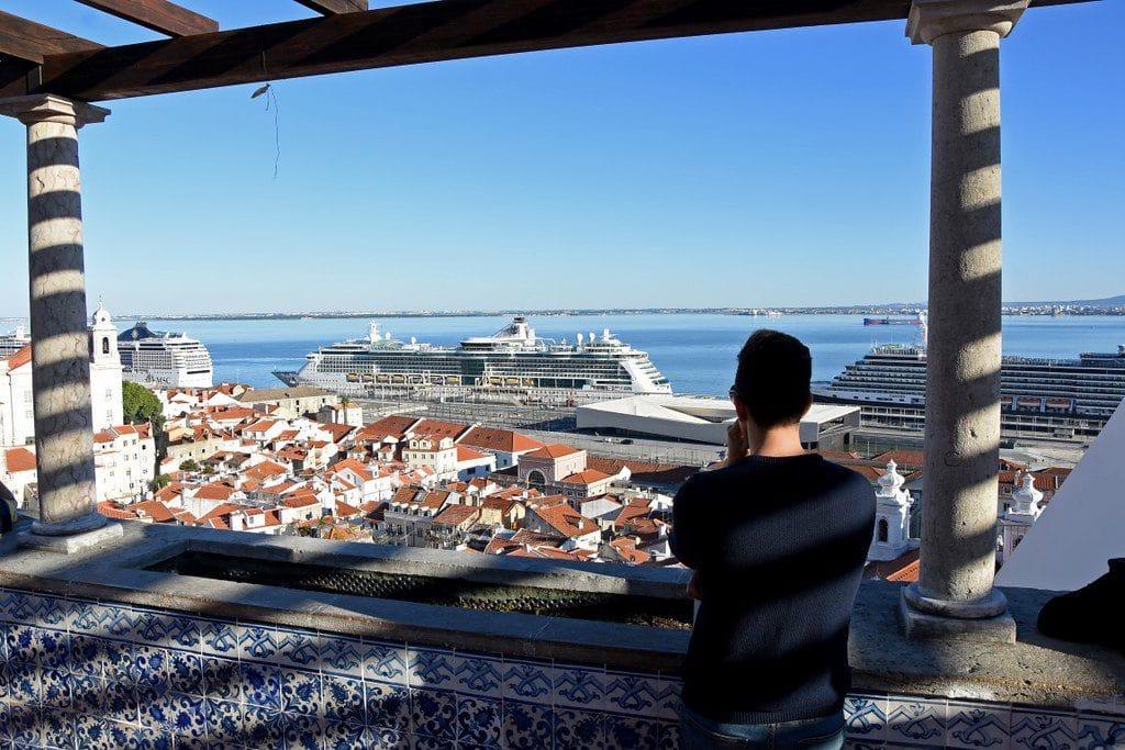 homem no miradouro de Santa Luzia em Lisboa, com vista para o Terminal de Cruzeiros de Santa Apolónia