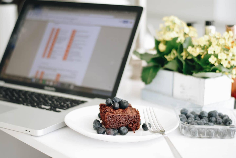 sobremesa de bolo de chocolate perto de um computador portátil Mac