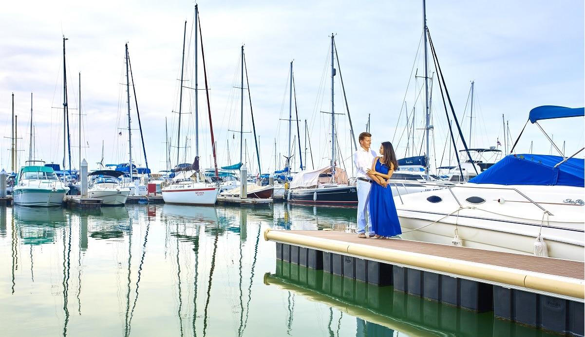 casal de namorados junto a um porto de embarcações