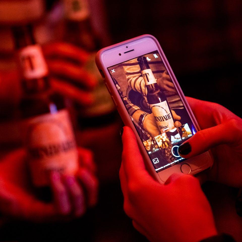 homem a tirar uma fotografia a uma cerveja trindade