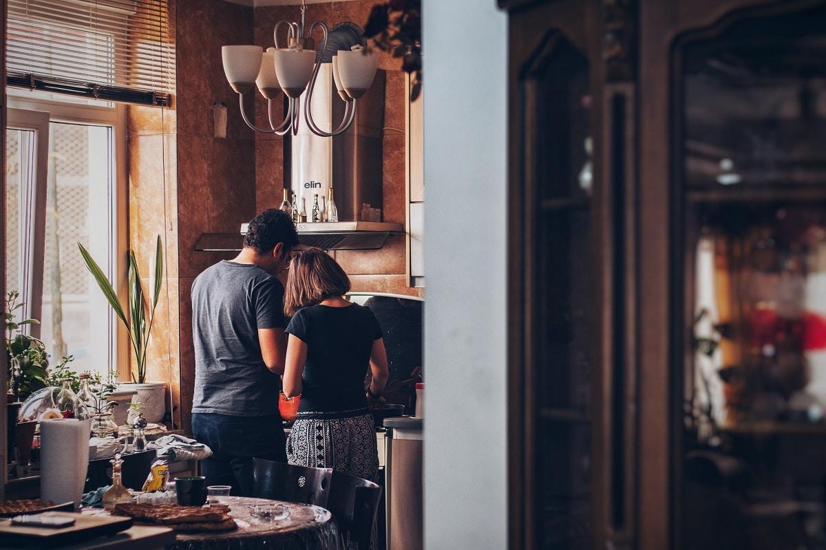 casal a preparar o pequeno-almoço enquanto trabalha a partir de casa