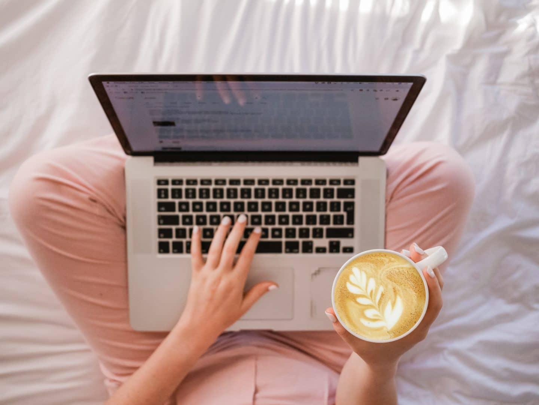mulher em cima da cama a ler no computador