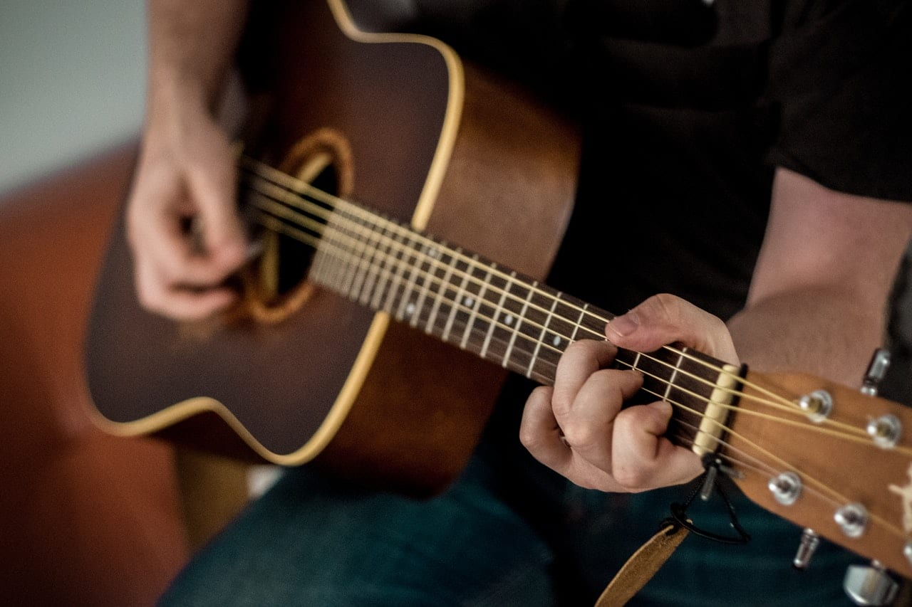 person-playing-brown-guitar