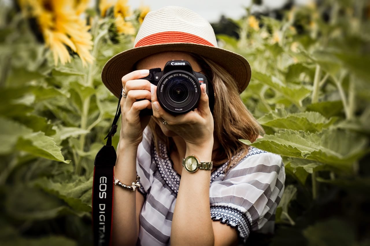 selective-focus-photography-of-woman-holding-dslr-camera