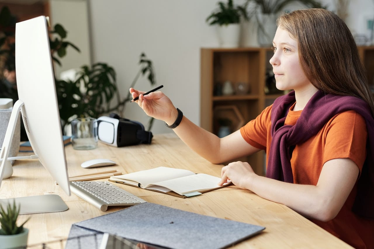 girl-holding-pencil-while-looking-at-imac