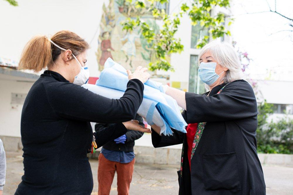 duas mulheres fazem a entrega de máscaras de proteção coronavírus