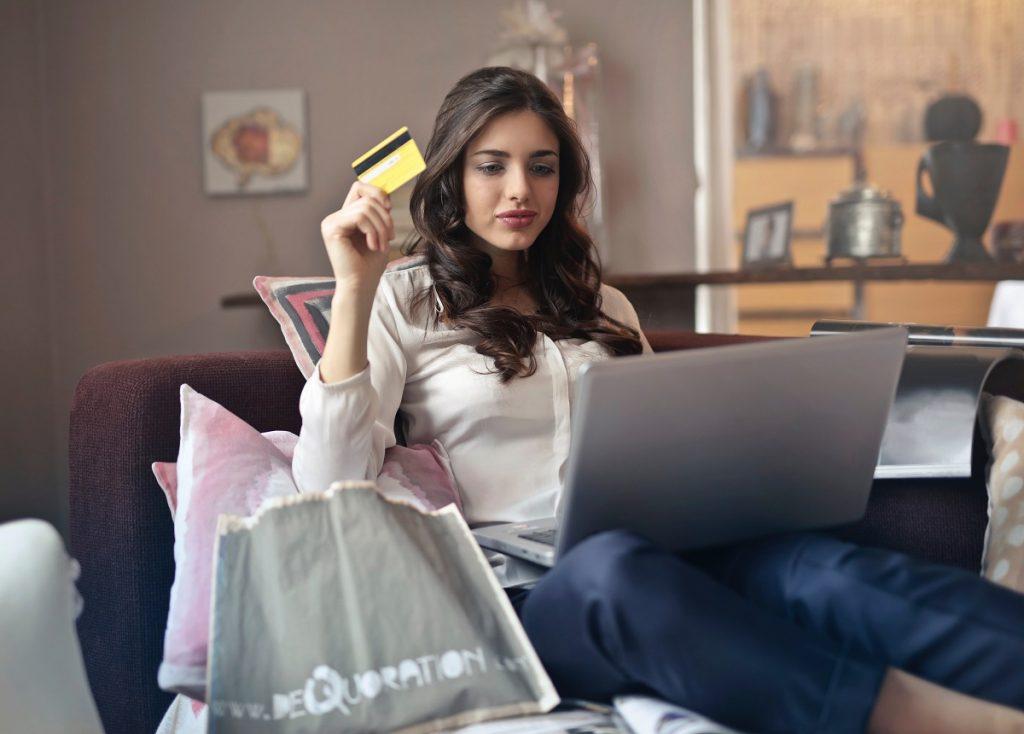 mulher segura cartão de crédito enquanto trabalha com computador portátil