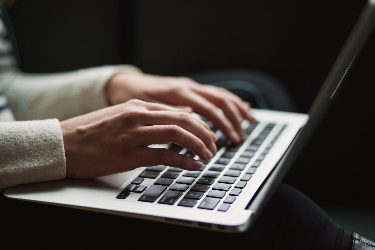 mulher a escrever num computador portátil