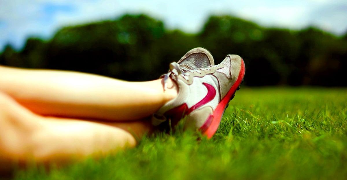 mulher a descansar depois de correr no jardim