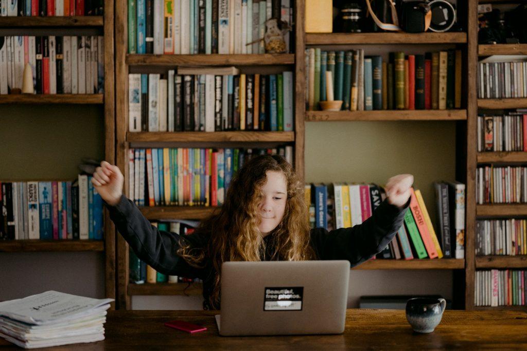 jovem rapariga com computador portátil a estudar em casa