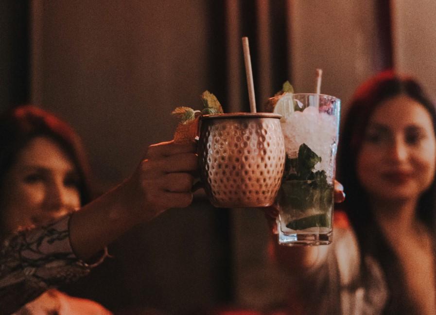 dua mulheres a brindarem com cocktails