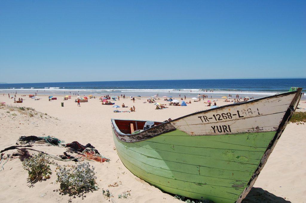 praia em lisboa com lancha em primeiro plano