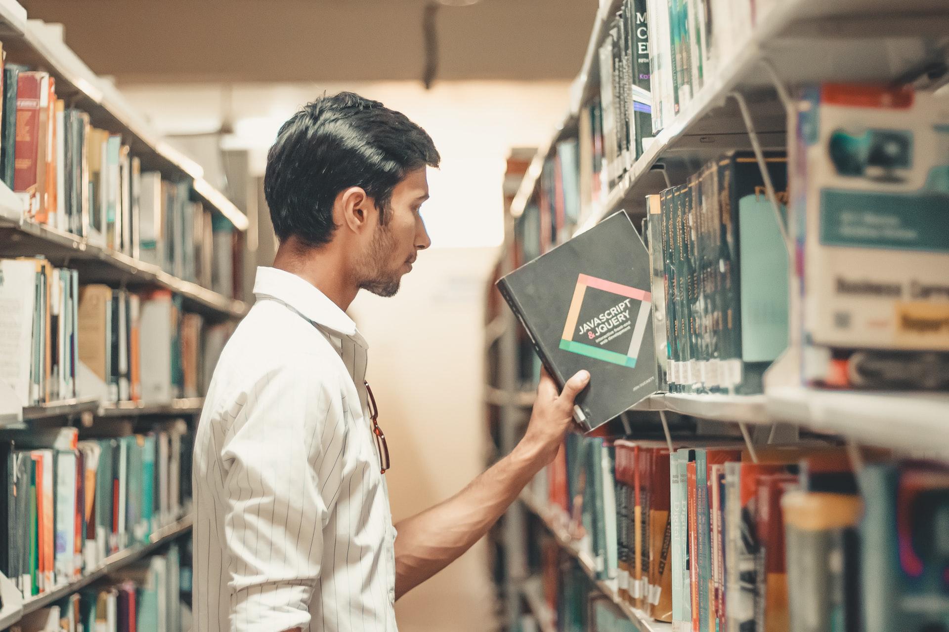 homem escolhe livro numa estante de biblioteca