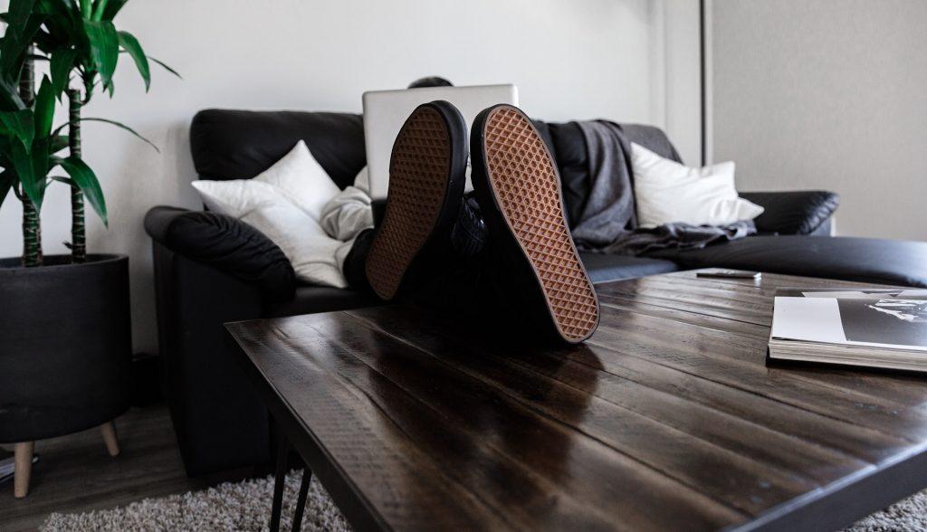 homem sentado no sofá com computador portátil