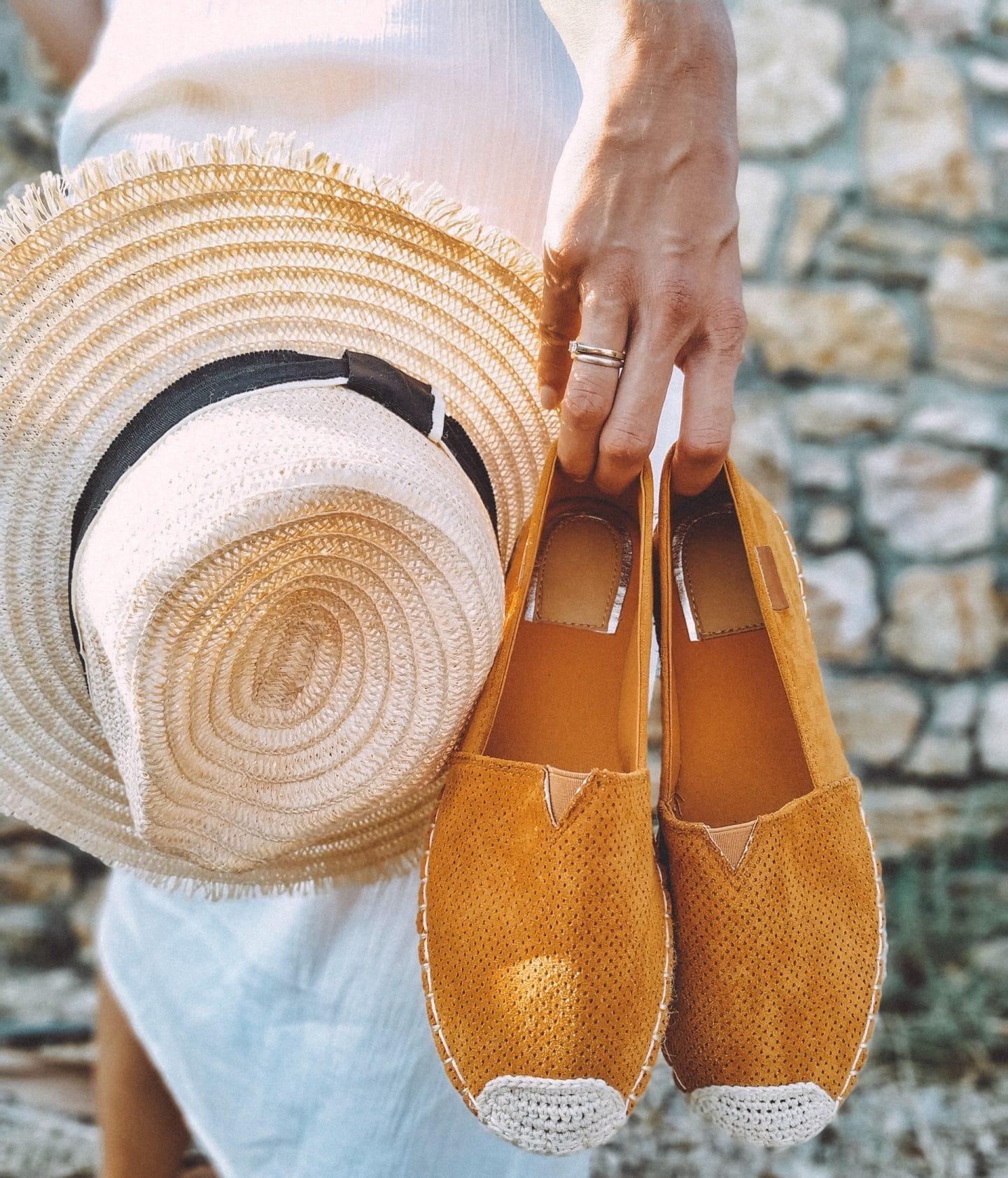 mulher com umas alpercatas e um chapéu de palha na mão