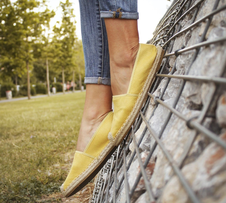 mulher com alpercatas calçadas num jardim