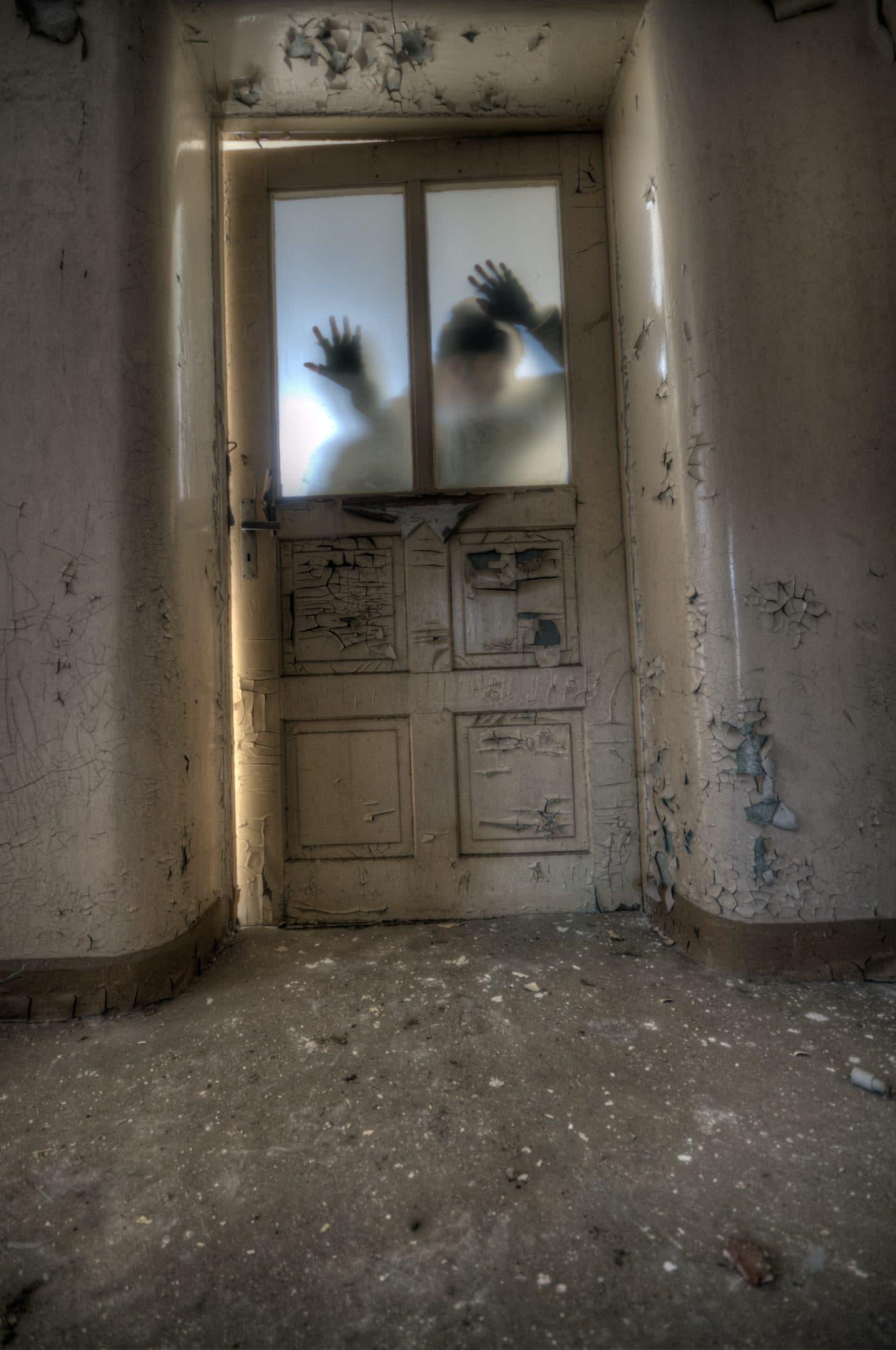 pessoas a tentar entrar através de uma porta num sítio assustador