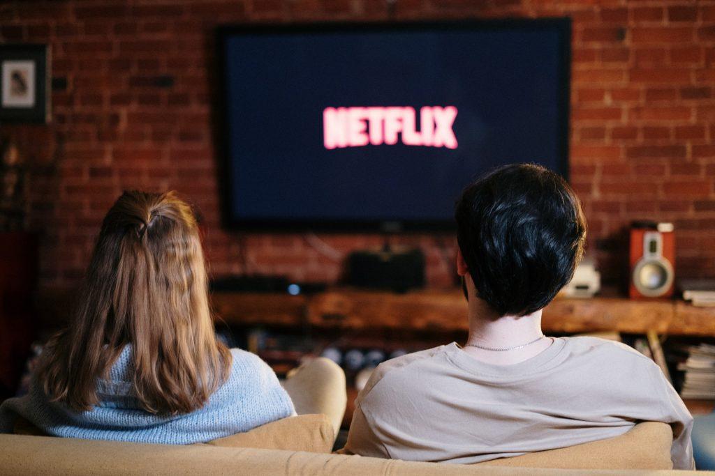 casal sentado no sofá a ver netflix