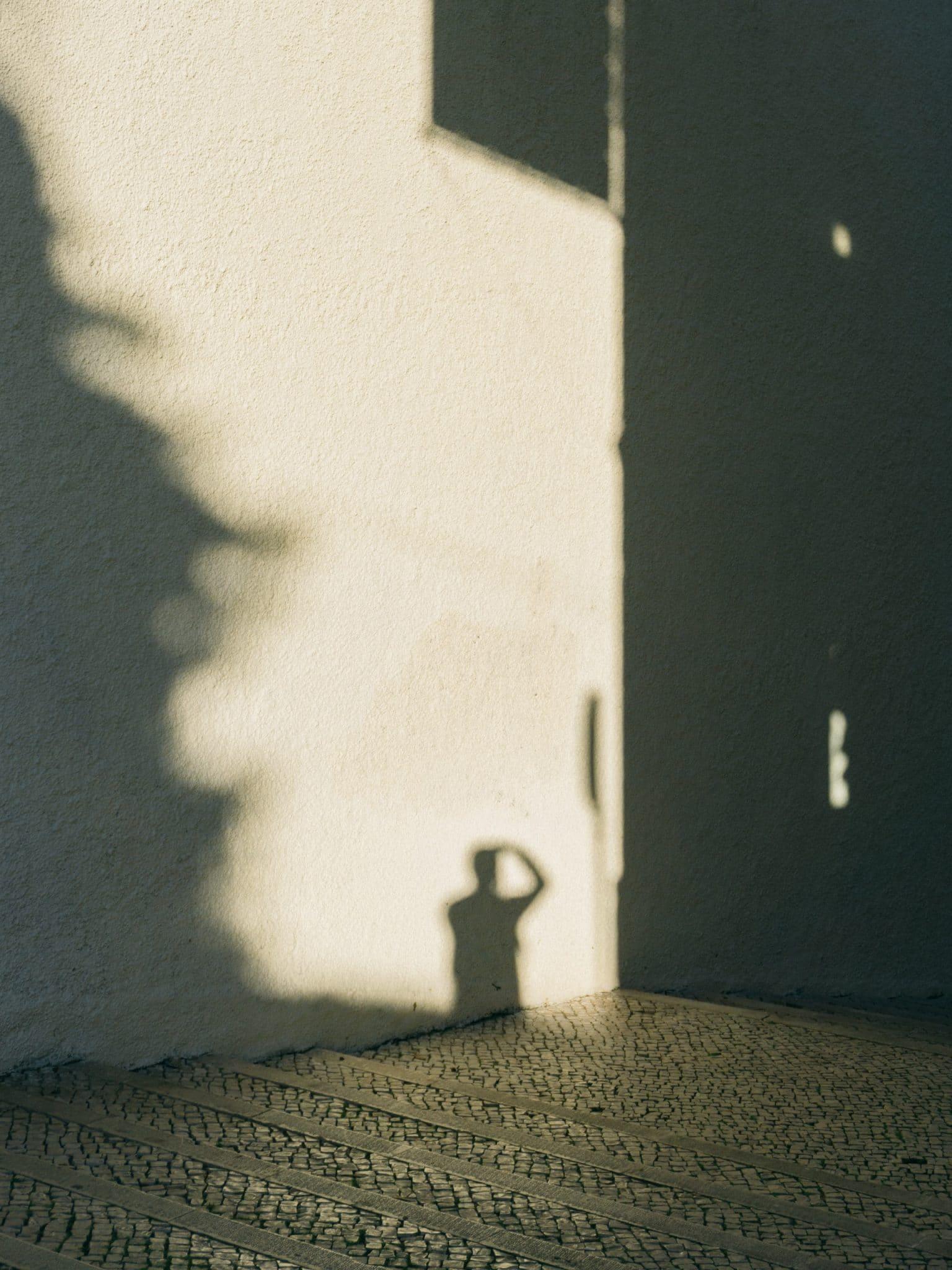 sombra de pessoa a tirar uma fotografia nas ruas de lisboa