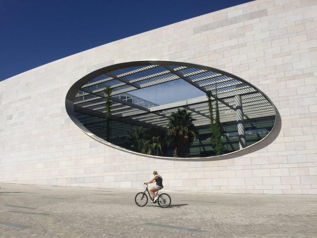 mulher a andar de bicicleta numa ciclovia em lisboa