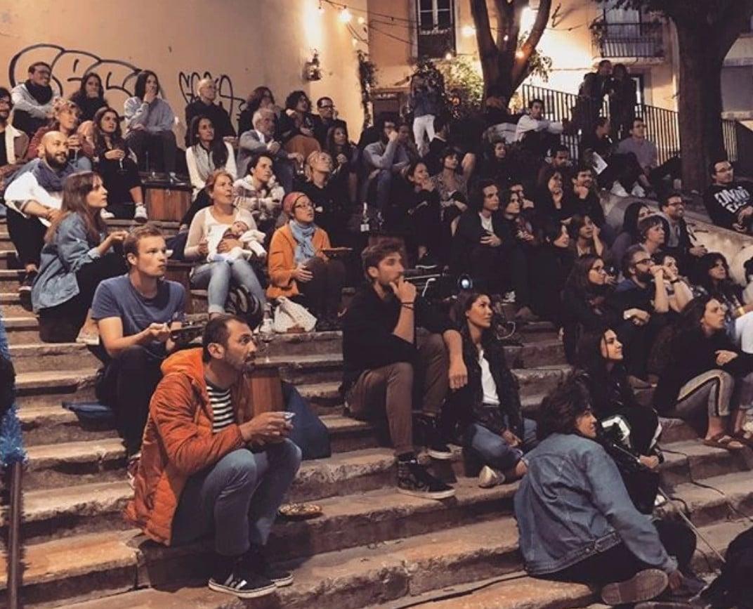pessoas nas escadas de um bairro de lisboa a ver um filme num estendal
