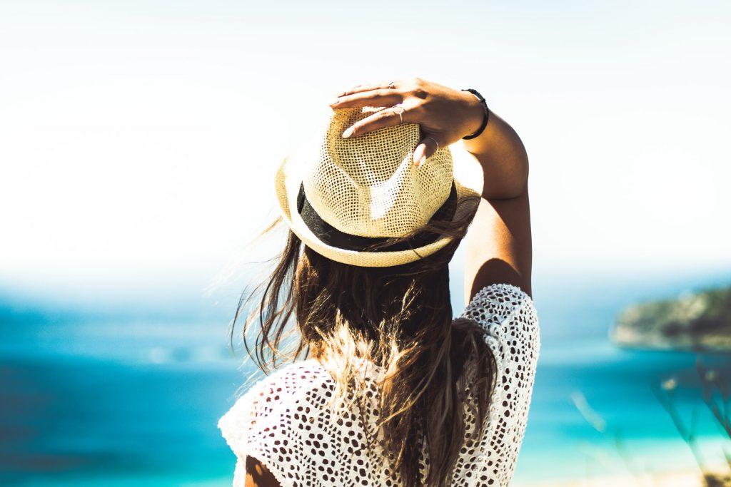 mulher com chapéu de palha em frente a uma praia