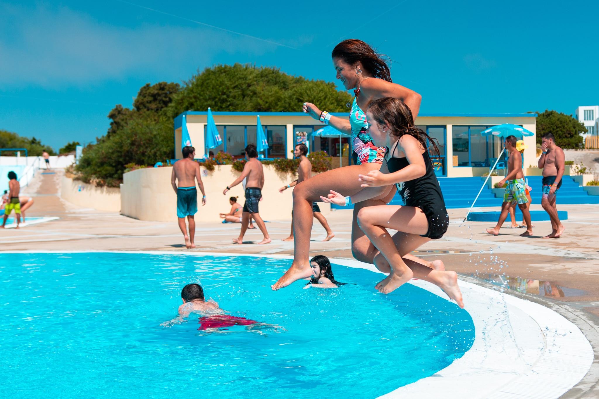 crianças a saltar para a piscina