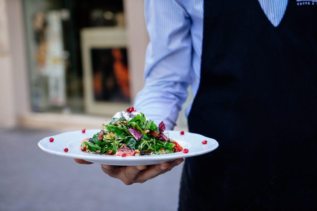 empregado de mesa a servir uma salada