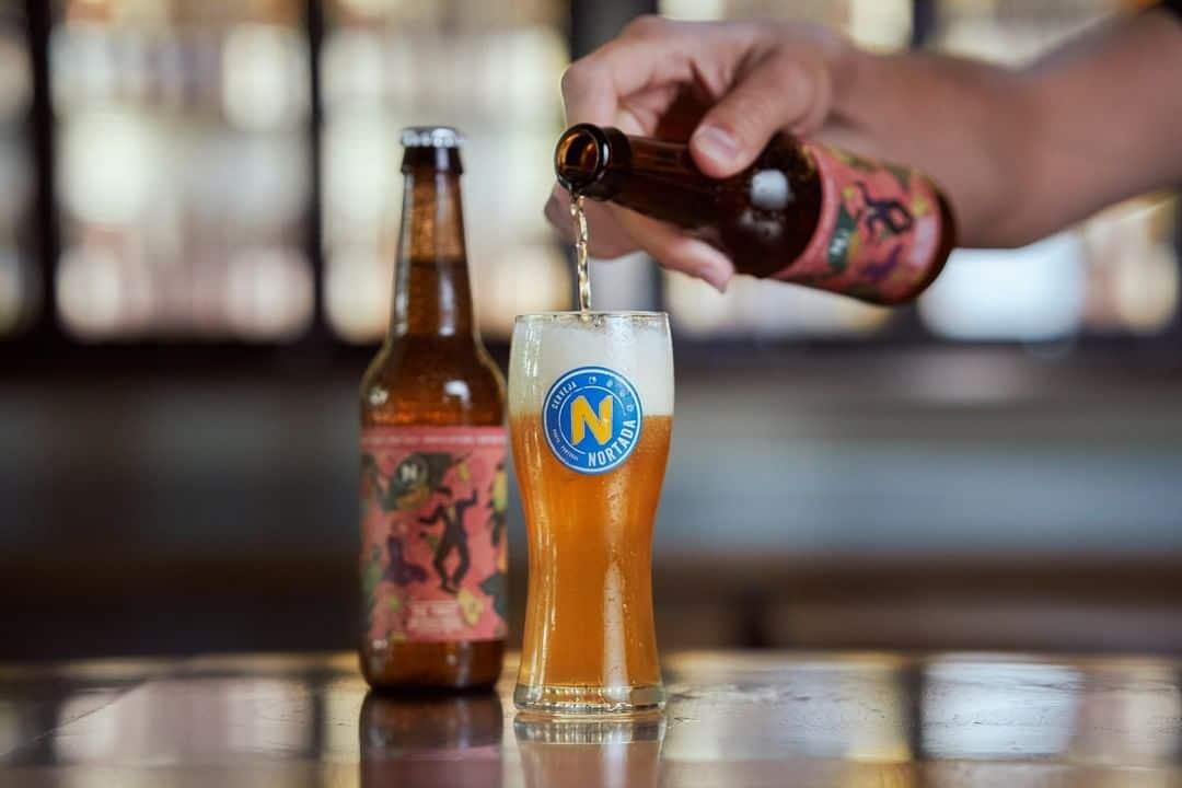 pessoa a colocar cerveja nortada num copo