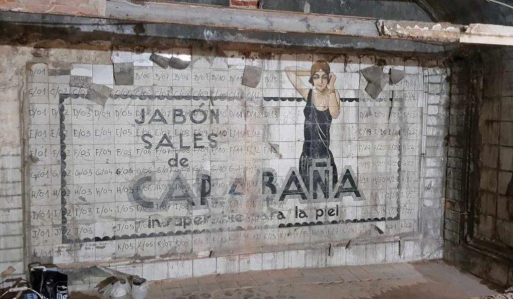Aparece un anuncio de los años 20 tras los muros del Metro de Sevilla