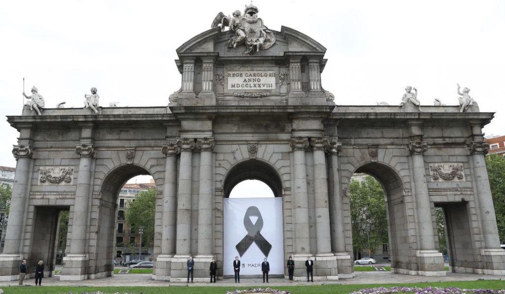 Un crespón negro cuelga de la Puerta de Alcalá en recuerdo de los fallecidos por Covid-19