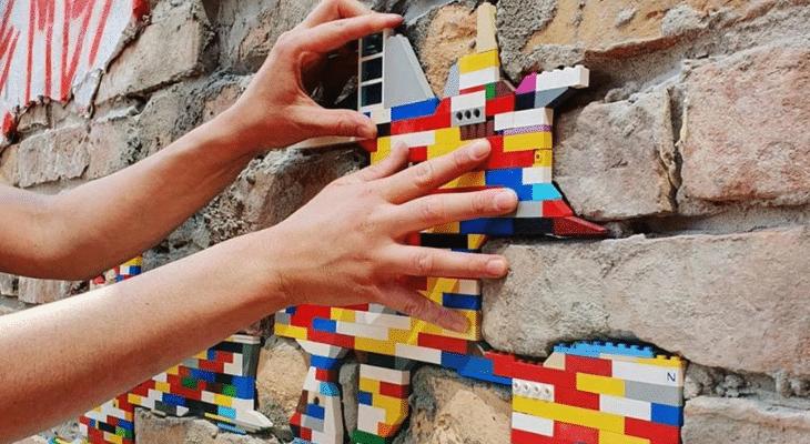 Street art : Il répare et colore les murs avec des Lego !