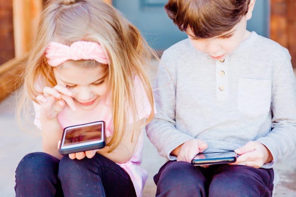 duas crianças a usarem o telemóvel para entretenimento