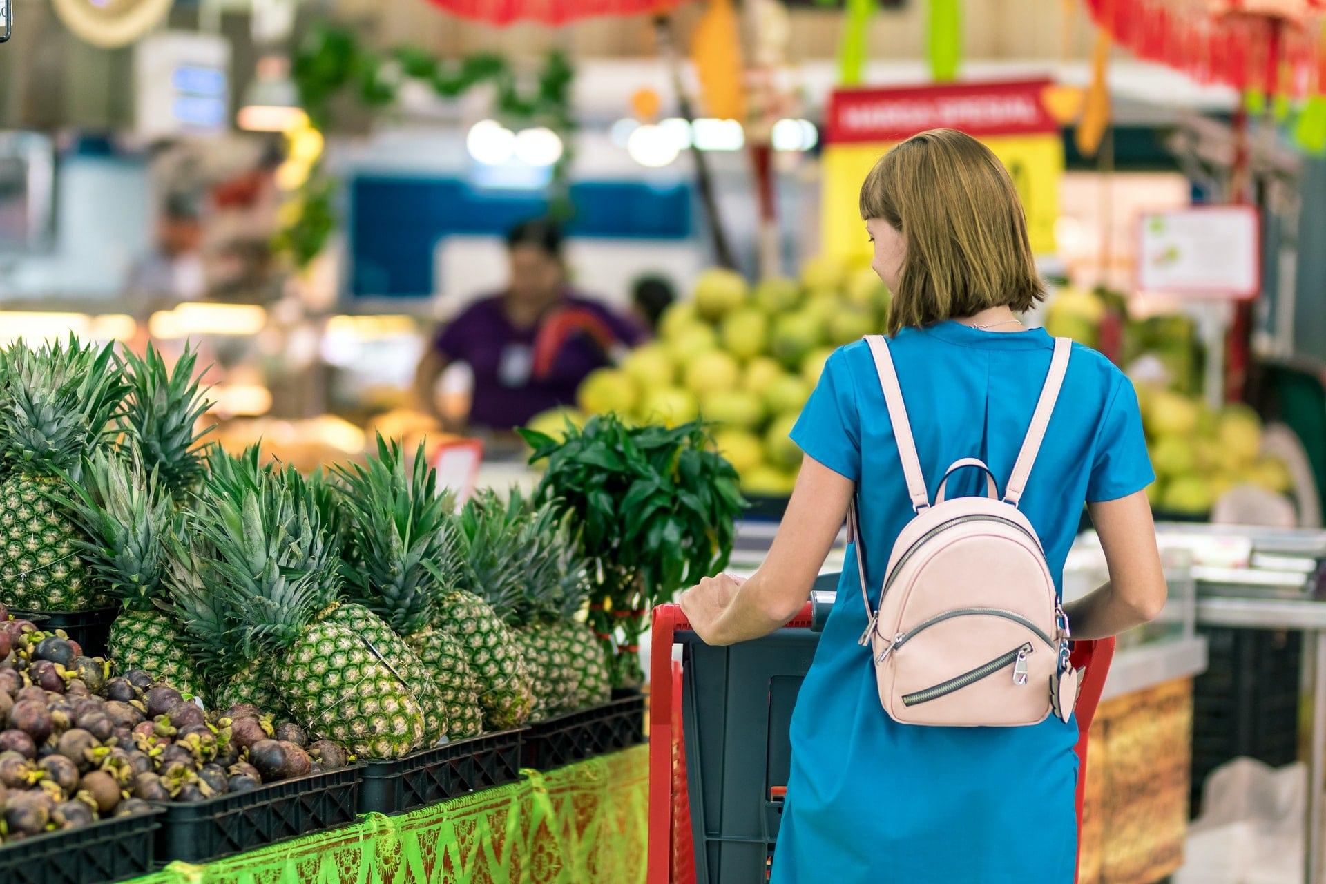 woman-standing-beside-pineapple-fruits