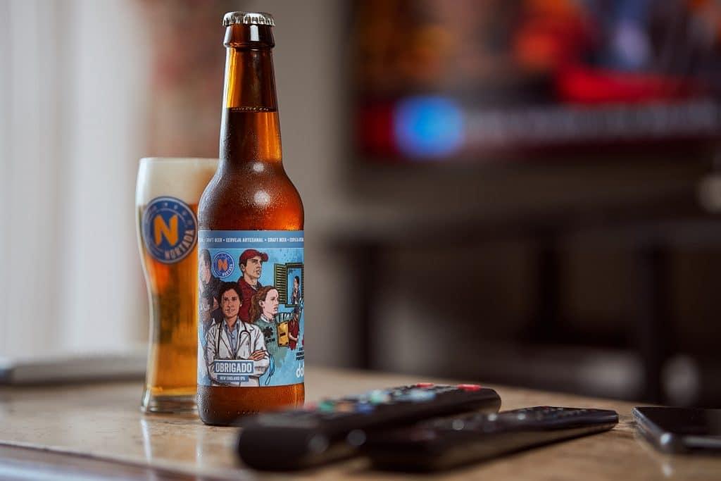 garrafa de cerveja nortada junto a comandos de tv