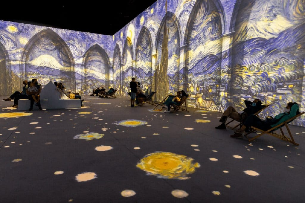 Van Gogh: The Immersive Experience exhibition. Image of The Starry Night on walls and floor of museum.
