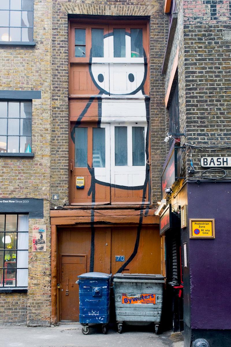 Tall stick man mural keeping watch