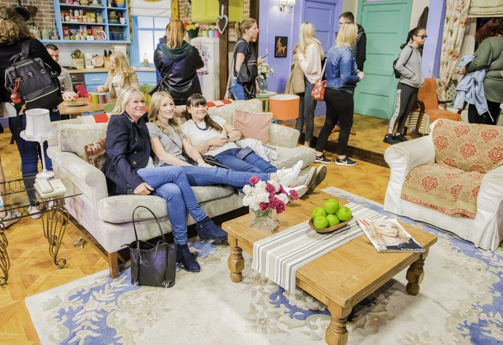 Three friends relax on a sofa at FriendsFest