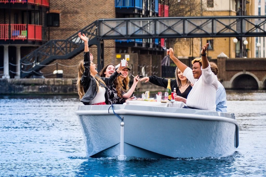 A group of friends wave from a GoBoat on a voyage around Canary Wharf.