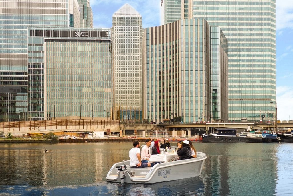 A GoBoat cruises around the waters of Canary Wharf with skyscrapers in the background.