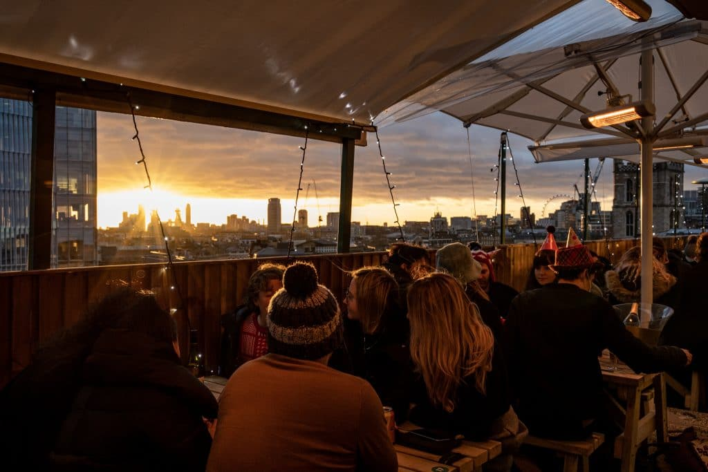 Revellers drink and watch the sunset at London Bridge Rooftop