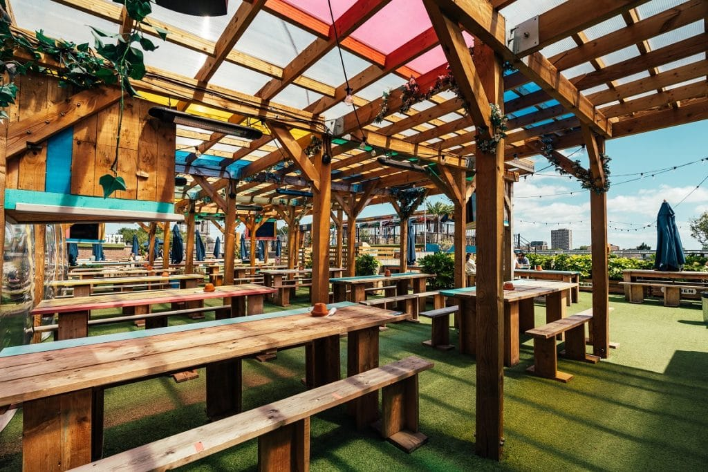 Empty chairs beneath a canopy at Skylight rooftop bar.