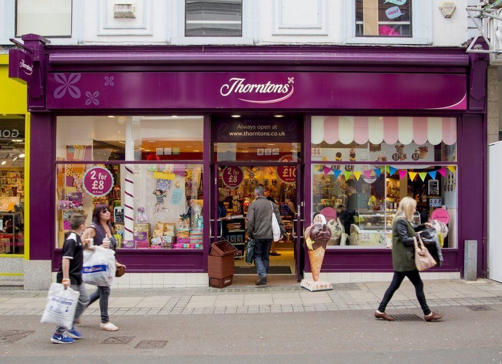 A Thorntons storefront with customers entering and pedestrians walking by