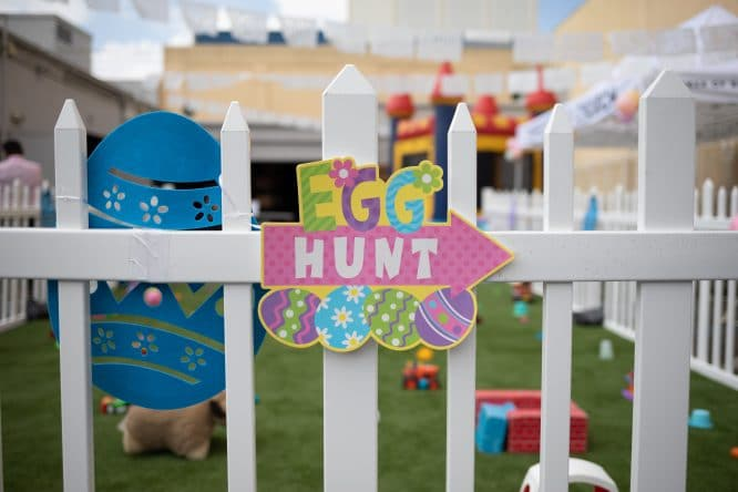 Easter egg hunt sign on a white fence