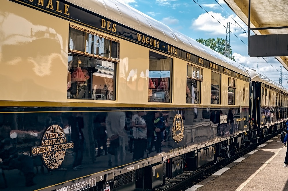 The Orient Express gleams in the sunlight as it stands at a train station.
