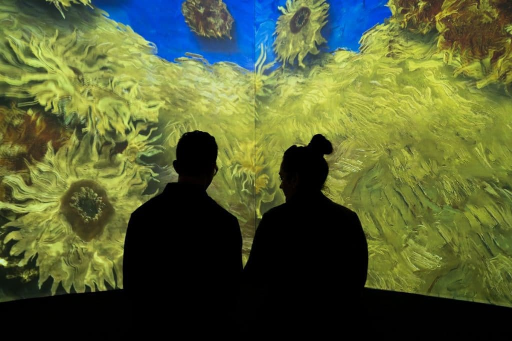 Two people watch the sunflowers bloom at London's immersive Van Gogh exhibition.