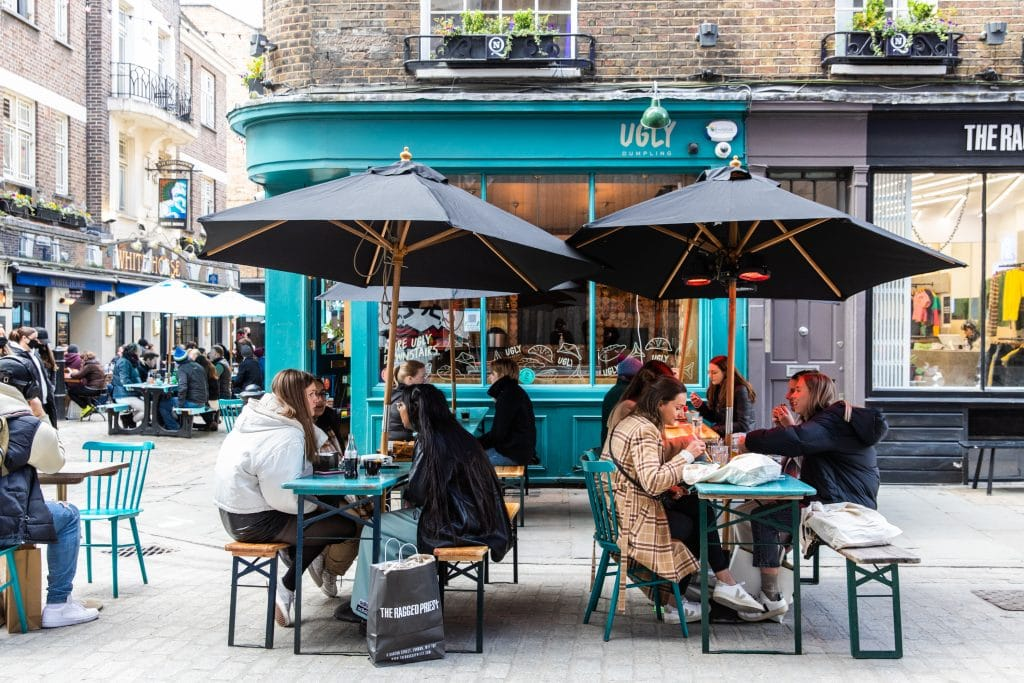 Diners sit at an outdoor table in the Carnaby and Soho outdoor dining space