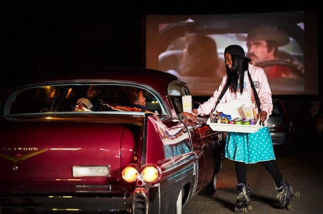 Drive In Film Club skaters serving snacks to guests in their car